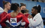 Simone Biles talked to teammates Grace McCallum, Jordan Chiles and Suni Lee before the uneven bars competition.