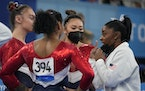 Simone Biles of the United States, right, talked to teammates Jordan Chiles, back to camera, Suni Lee and Grace McCallum, left, prior to the uneven ba