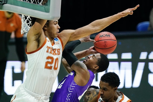 Texas' Jericho Sims (20) blocked the path of Abilene Christian's Mahki Morris during an NCAA tournament game March 20 in Indianapolis.