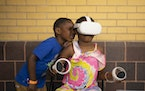 Nicholas Smith Jr., 5, tried to see what Laylay Comodore, 6, was experiencing via a virtual reality game offered through St. Paul's Summer Swarm pro