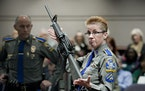 In this Jan. 28, 2013, file photo, firearms training unit Detective Barbara J. Mattson, of the Connecticut State Police, holds up a Bushmaster AR-15 r
