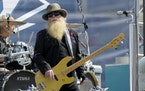 FILE - Dusty Hill, of ZZ Top, performs before the start of the NASCAR Sprint Cup series auto race in Concord, N.C., May 24, 2015.