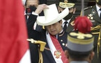 Peru's newly sworn-in President Pedro Castillo puts his hat back on after taking it off momentarily to acknowledge the Peruvian flag held by soldier