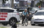 A cyclist passes cars at a standstill along West Colonial Drive in Orlando, Fla., Thursday, July 29, 2021, as residents wait in line for COVID-19 test