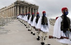 Presidential Guard members walk in front of the Parthenon in Athens.