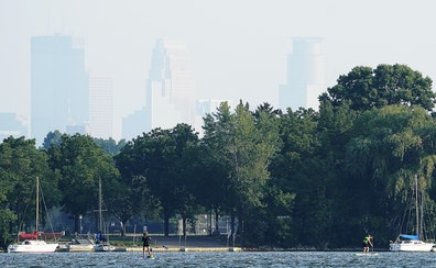 Haze from wild fires burning in Canada obscured the Minneapolis skyline as water boarders paddled along Lake Nokomis Thursday in Minneapolis.