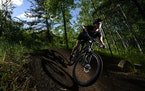 """Kate Swanson, a helicopter flight nurse from Brainerd and avid mountain biker, cut around a berm on the """"Drawpoint Trail"""" Tuesday at Cuyuna Countr"""