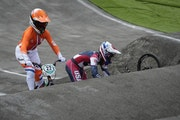 Alise Willoughby of the United States retrieves her bike after crashing, as Merel Smulders of the Netherlands passes on the left, in the BMX Racing se