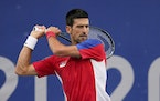 Novak Djokovic, of Serbia, returns to Alexander Zverev, of Germany, during the semifinal round of the men's tennis competition at the 2020 Summer Ol