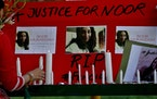 A women's rights activist places a candle beside a poster with pictures of Noor Mukadam during a vigil to pay tribute to Noor and other domestic vio