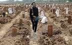 A woman walks among the graves of COVID-19 victims at the Rorotan Cemetery in Jakarta, Indonesia, on July 7. Across the country, the coronavirus pande