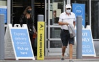 FILE - In this July 30, 2020 file photo, shoppers wear face masks as they leave a Walmart store in Vernon Hills, Ill. Walmart is reversing its mask po