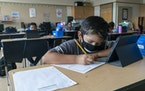 A student wears a face mask while doing work at his desk at the Post Road Elementary School, in White Plains, N.Y., on Thursday, Oct. 1, 2020. U.S. he
