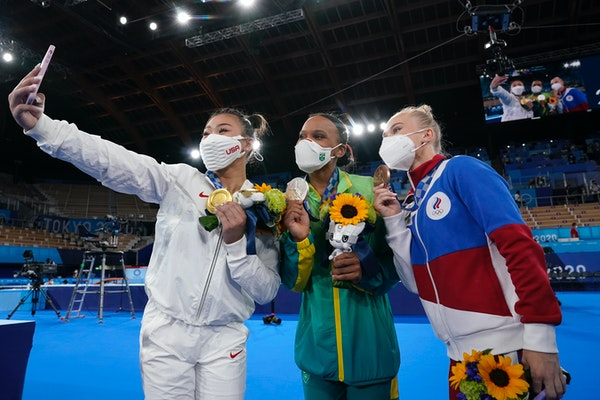 A very 2021 moment: Masks, selfies and some impromptu bonding. From left, gold medalist Suni Lee of St. Paul, Brazil's Rebeca Andrade and Russian An