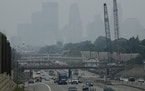 Traffic moved along Interstate 35W, with downtown Minneapolis enveloped by a smoky haze, as seen from the East 46th Street overpass.