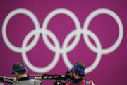 Sergey Kamenskiy, right, of the Russian Olympic Committee, competes in the men's 10-meter air rifle at the Asaka Shooting Range in the 2020 Summer O
