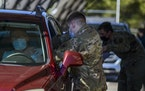 FILE - Soldiers administer COVID-19 vaccines at a drive-thru vaccination site in Fort Bragg, N.C., Feb. 24, 2021. New vaccine rules for federal worker