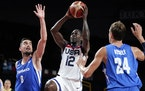 The United States' Jrue Holiday (12) drives to the basket between the Czech Republic's Tomas Satoransky (8) and Jan Vesely (24) during a men's b