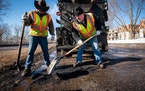 Street service workers Bradley Therres, left, and Lance Hamby fill potholes on Shepard Road in 2019. LEILA NAVIDI • leila.navidi@startribune.com