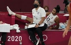 United States' Jordan Thompson, rear, lies injured on the bench during the women's volleyball preliminary round match against the Russian Olympic