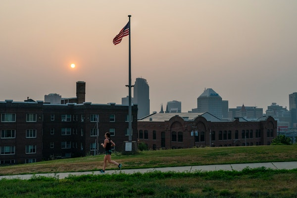 A person rans down Summit Avenue in St. Paul as the sun rose Saturday amid smoke from Canadian wildfires.