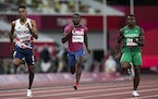 Trayvon Bromell, of United States, center, finishes a heat in the men's 100-meter run at the 2020 Summer Olympics