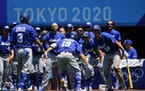 Israel's Danny Valencia (19) celebrates with his teammates after hitting a three-run home run during a baseball game against Mexico.