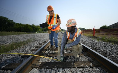 Maria Workman, a foreman working with PSG Contracting, watched as labor apprentice Francis Kirunda took measurements on the Southwest Light Rail line.