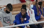 Simone Biles, of the United States, sits at the stands with teammates during the artistic gymnastics men's apparatus final at the 2020 Summer Olympi