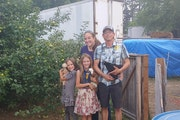 Chelsea and Matt Brennan, with daughters Elizabeth (left) and Allison, have been cited by Sherburne County officials for having too many vehicles stor