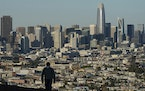 FILE - In this Dec. 7, 2020, file photo, a person wearing a protective mask walks in front of the skyline on Bernal Heights Hill during the coronaviru