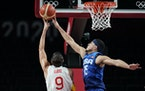 United States' Devin Booker (15), right, tries to block a shot by Spain's Ricky Rubio (9) during the men's quarterfinal between the United State