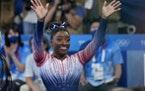 Simone Biles, of the United States, waves after performing on the balance beam during the artistic gymnastics women's apparatus final at the 2020 Su