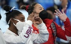 Simone Biles and Suni Lee wave after finishing their balance beam routines.