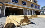 In this June 24, 2021 file photo, lumber is piled at a housing construction site in Middleton, Mass. Wood prices have skyrocketed over the last year,