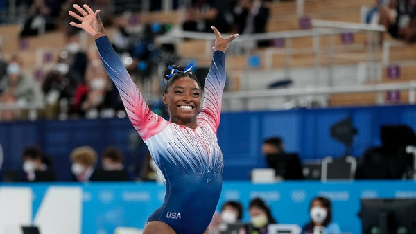 Simone Biles flashed a smile after completing her balance beam routine Tuesday at the Tokyo Olympics.