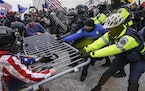 In this Jan. 6, 2021, file photo violent insurrectionists loyal to President Donald Trump hold on to a police barrier at the Capitol in Washington. Th