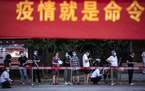 """Residents line up for Covid-19 tests near a banner with the words """"Epidemic is the Order"""" in Wuhan in central China's Hubei province Tuesday, Au"""