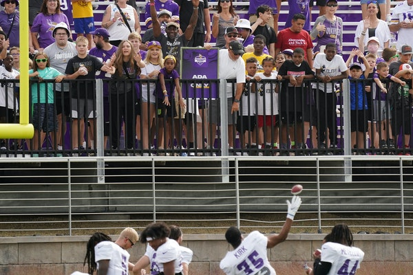 Vikings players throw mini footballs to fans after practice Wednesday.