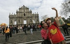"""In 2014, tourists take selfies at """"The Ruins of St. Paul's"""" a famous tourist spot, in Macao. Four new COVID-19 infections have sparked concern a"""