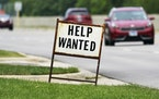 A help wanted sign is displayed at a gas station in Mount Prospect, Ill., Tuesday, July 27, 2021. The number of Americans applying for unemployment be