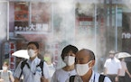 People wearing face masks to protect against the spread of the coronavirus walk under a water mist in Tokyo Thursday, Aug. 5, 2021. New cases surge in
