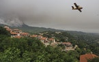 An aircraft operates as flames burn a forest during a wildfire in Kourkouloi village on the island of Evia, about 150 kilometers (93 miles) north of A