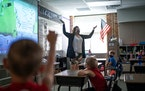 First-graders raised their hand to offer an answer during Katie Nelson's summer school class at Vista View Elementary in Burnsville.