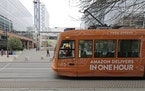 FILE - This Nov. 13, 2018 file photo a South Lake Union streetcar with an advertisement for Amazon.com's same-day delivery service passes by an Amaz
