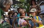 Kestrel Fen, 8, right, and Avea Myslajek Marks, 8, center, try to choose a vegetable to take home as Karen Clark, left, of Women's Environment Insti