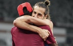 Gianmarco Tamberi, of Italy, embraces fellow gold medalist Mutaz Barshim, of Qatar, after the final of the men's high jump at the 2020 Summer Olympi