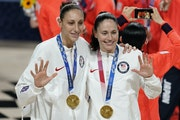 Sue Bird, right, and Diana Taurasi pose with their gold medals during the medal ceremony for women's basketball at the 2020 Summer Olympics