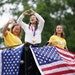 Sunisa Lee, center, with her mom Yeev Thoj and sister Shyenne Lee, waved to the crowds during a parade Sunday in the East Side St. Paul neighborhood w