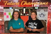 Miranda Klassen, 14, (left) and her sister Ava, 11, pose inside a cutout in the lobby of this summer's Grand American trap shooting competition in S